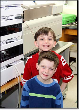 Connor (back) and Kellen Brown standing beside the machine that screened their bloodspots years ago – the very machine that saved their lives.
